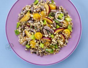 Insalata di farro con borlotti, prugne, peperoni, pomodorini e semi